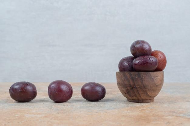 Ameixas maduras roxas em uma tigela sobre fundo de mármore.