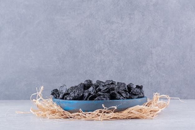 Ameixas pretas secas em um copo de comida na superfície de concreto