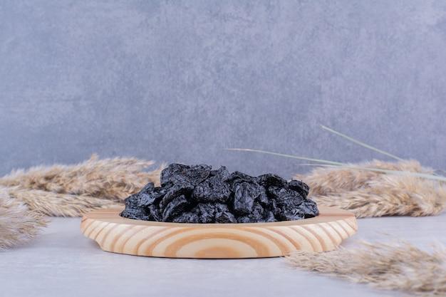 Ameixas pretas secas isoladas em uma travessa de madeira