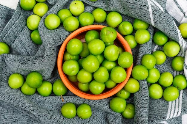 Ameixas verdes carnudas em uma tigela de laranja close-up na toalha de cozinha