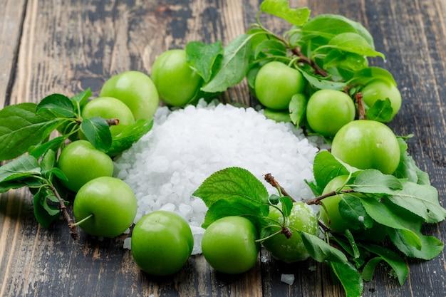 Ameixas verdes com cristais de sal, deixa a vista de alto ângulo em uma parede de madeira