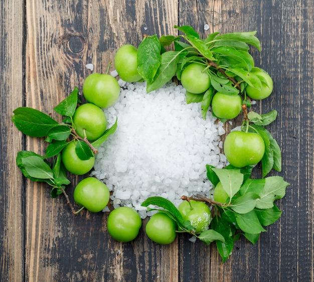 Ameixas verdes com cristais de sal, folhas na parede de madeira, plana leigos.