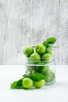 Ameixas verdes com folhas em um mini frasco de vidro na parede branca e suja, vista lateral.