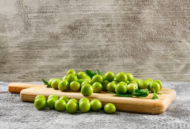 Ameixas verdes com folhas em uma placa de corte em cinza e marrom, vista lateral suja.