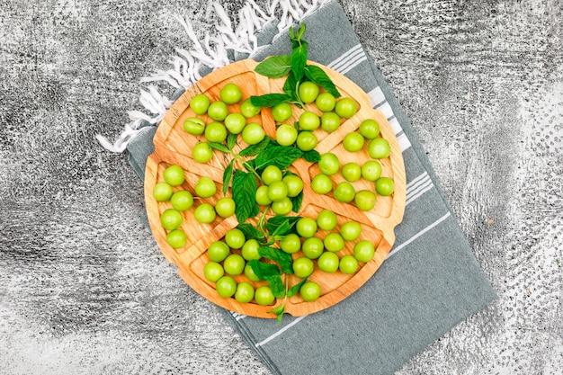 Ameixas verdes com folhas em uma placa de madeira redonda no pano de grunge e piquenique. configuração plana.