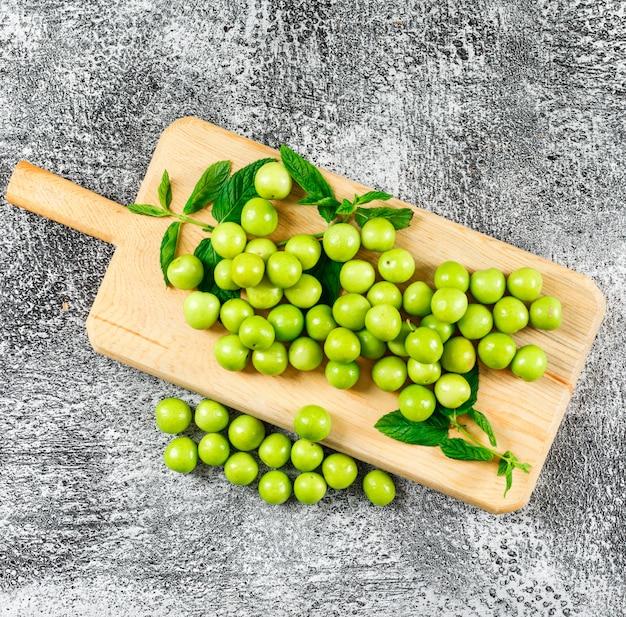 Ameixas verdes com folhas em uma tábua de madeira plana leigos em cinza sujo