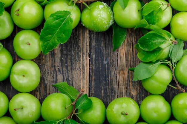 Ameixas verdes com folhas na parede de madeira, configuração plana.