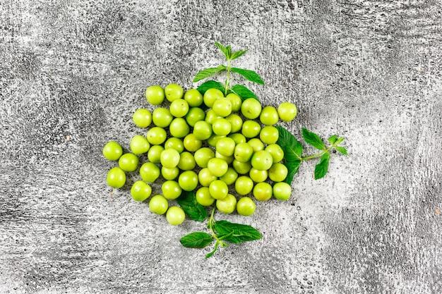 Ameixas verdes com folhas no grunge. vista do topo.