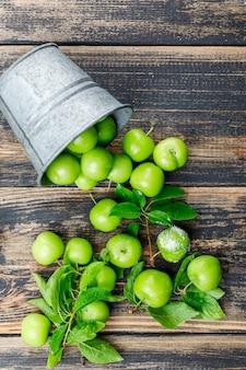 Ameixas verdes dispersas com folhas, sal de um mini balde na parede de madeira, vista superior.