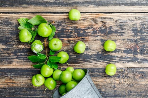 Ameixas verdes dispersas do mini balde com folhas, sal na parede de madeira, vista superior.