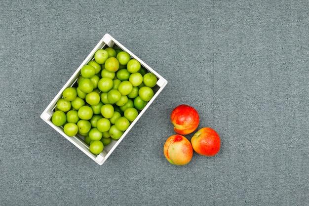 Ameixas verdes em uma tigela branca retangular com pêssegos frescos em cinza. configuração plana.