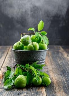 Ameixas verdes frescas em um mini balde com vista lateral de folhas na parede de madeira e enevoada