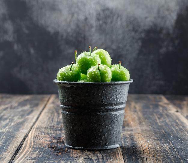 Ameixas verdes frescas em uma vista lateral para mini balde na parede de madeira e enevoada
