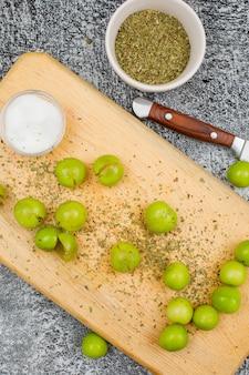 Ameixas verdes picantes com uma pequena barra de sal, tomilho seco e uma faca de fruta em uma placa de corte na superfície cinza grunge, close-up.