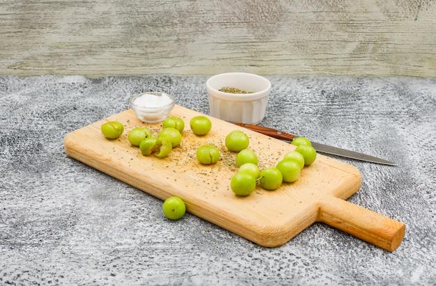 Ameixas verdes picantes em uma placa de corte com uma pequena barra de sal, tomilho seco e uma vista lateral de faca de fruta em uma superfície de grunge e parede de madeira