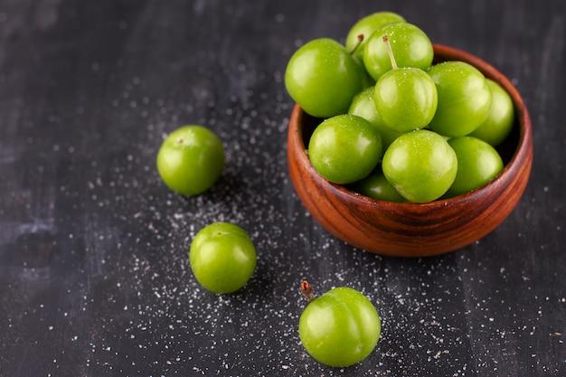 Ameixas verdes verdes com sal em uma mesa de madeira preta