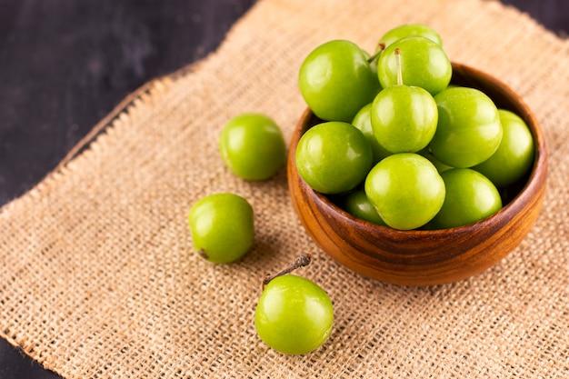 Ameixas verdes verdes em uma mesa de madeira preta