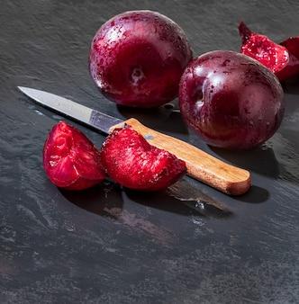 Ameixas vermelhas apetitosas e saudáveis, inteiras e cortadas em gomos de aspecto rústico sobre fundo preto.