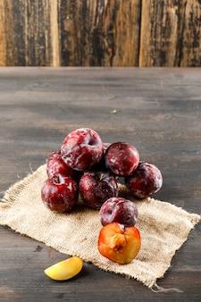 Ameixas vermelhas com pedaço de saco alto ângulo vista na superfície de madeira e suja