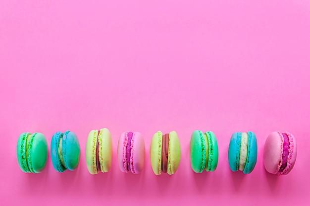 Amêndoa doce colorido rosa azul amarelo verde macaron ou bolo de sobremesa macaroon isolado em um pastel rosa da moda