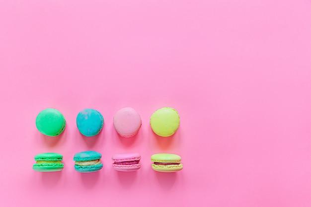 Amêndoa doce colorido rosa azul amarelo verde macaron ou bolo de sobremesa macaroon isolado no fundo rosa pastel na moda.