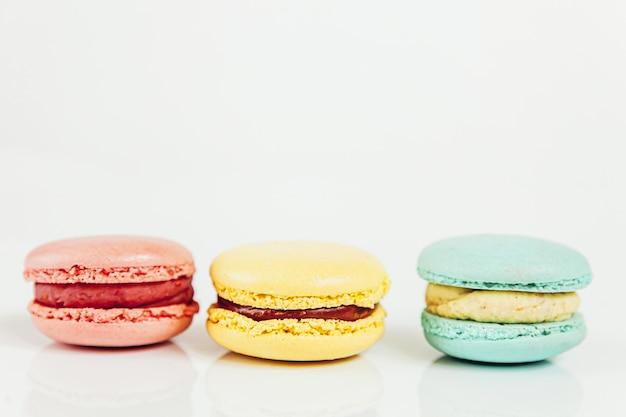 Amêndoa doce colorido rosa pastel azul amarelo macaron ou bolo de sobremesa macaroon isolado no branco