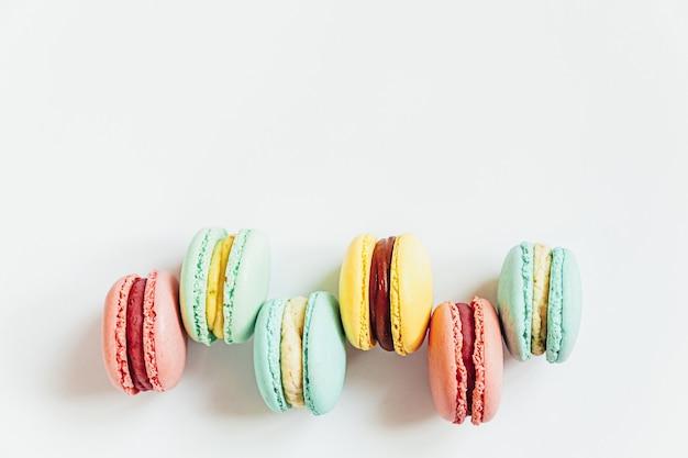 Amêndoa doce colorido rosa pastel azul amarelo verde macaron ou bolo de sobremesa macaroon isolado no branco