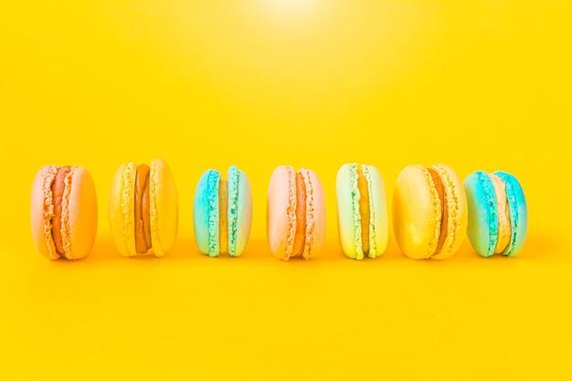 Amêndoa doce unicórnio colorido rosa azul amarelo verde macaron ou bolo de sobremesa macaroon isolado no amarelo