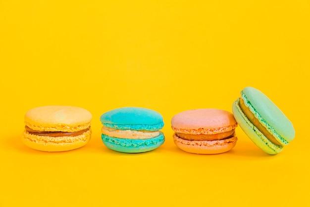 Amêndoa doce unicórnio colorido rosa azul amarelo verde macaron ou bolo de sobremesa macaroon isolado no fundo amarelo na moda moderno. biscoito doce francês. conceito de padaria de comida mínima. copie o espaço