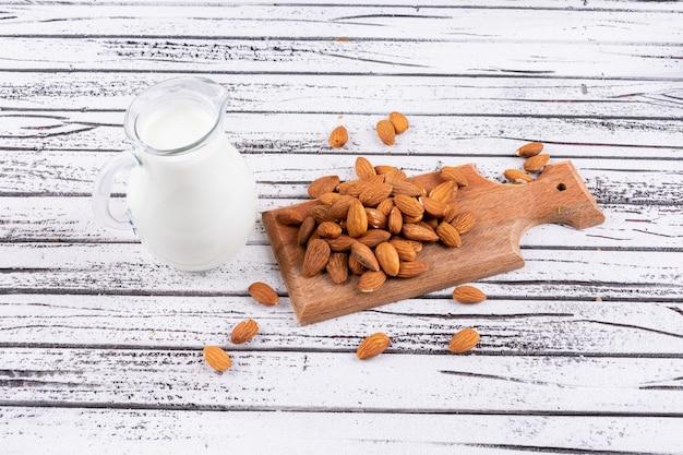 Amêndoa e leite sobre uma tábua de madeira sobre uma mesa de madeira branca