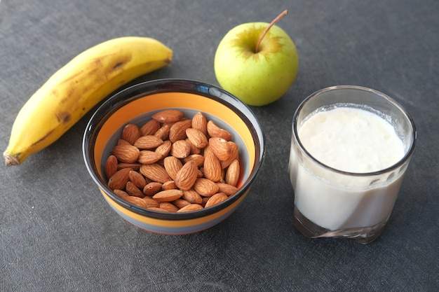 Amêndoa noz banana maçã e leite na mesa
