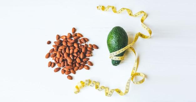 Amêndoa nozes deitado no prato. abacate com fita métrica. dieta para emagrecer. estilo de vida saudável. conceito vegano. nutrição apropriada. comida esportiva.