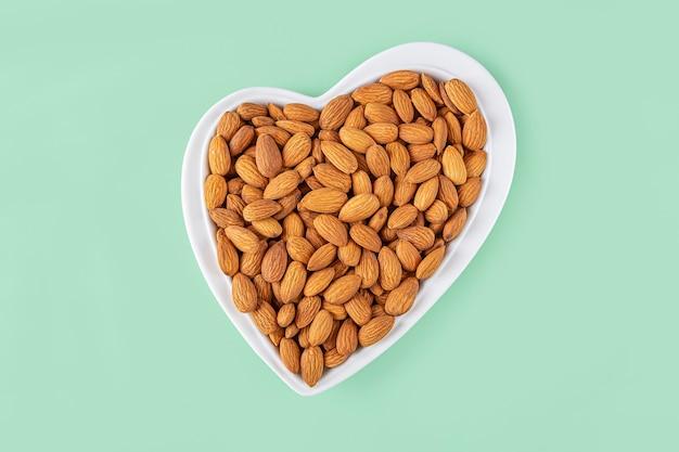 Amêndoas descascadas em placa em forma de coração sobre fundo verde. lanches vegetarianos saudáveis.
