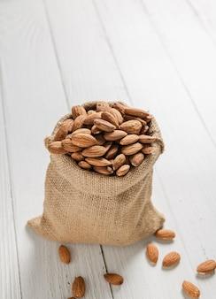 Amêndoas em sacos de cânhamo colocadas sobre piso de madeira branca