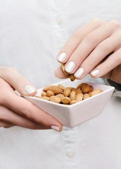 Amêndoas em tigela branca nas mãos de mulher