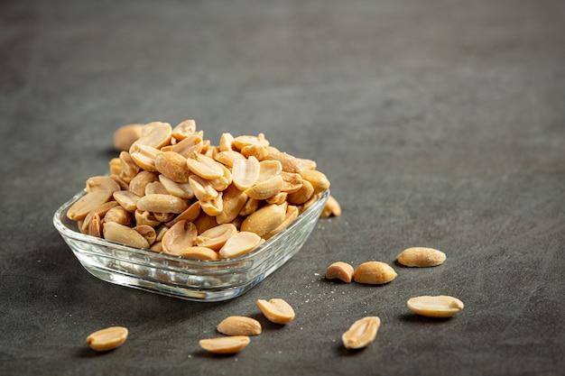Amendoim colocado em prato de vidro em fundo escuro