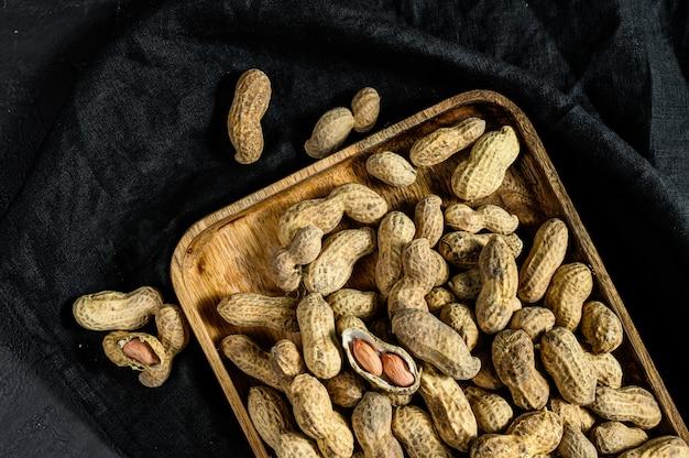 Amendoim com casca. amendoim cru orgânico. parede preta. vista do topo