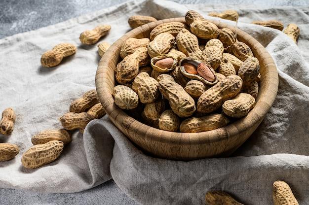 Amendoim com casca, amendoim cru orgânico, vista superior, espaço para texto
