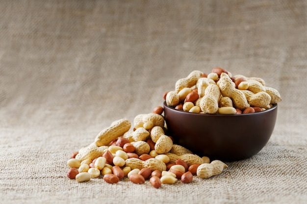 Amendoim com casca e descascado close-up em copos. amendoins torrados em casca e descascados em um pano marrom.