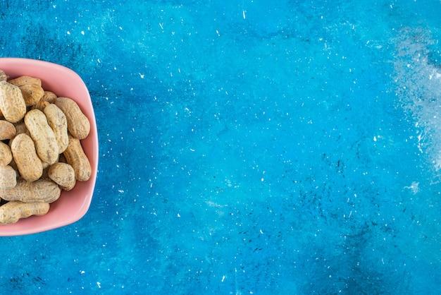 Amendoim com casca em um prato, na mesa azul.