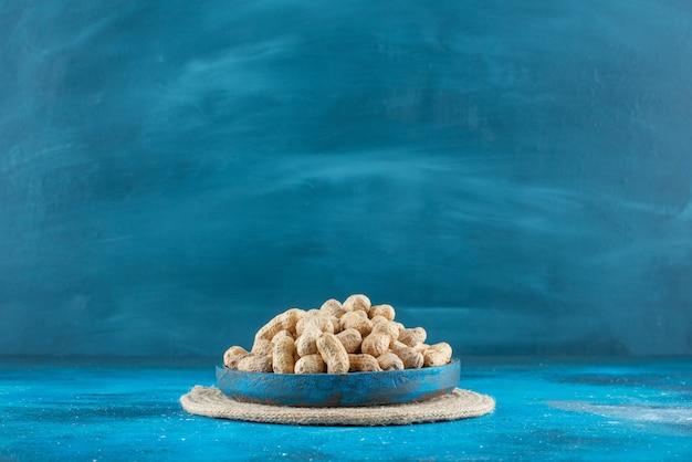Amendoim com casca em uma placa de madeira no tripé, sobre a mesa azul.