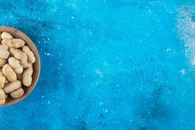 Amendoim com casca em uma tigela, na mesa azul.