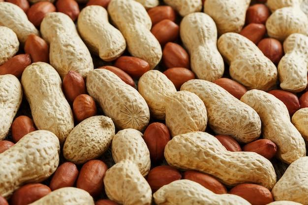 Amendoim com casca misturado com descascado, a textura do fundo alimentar de feijão