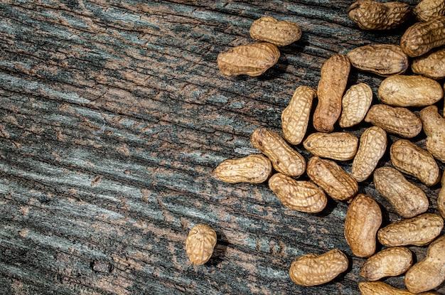 Amendoim com casca na madeira velha de textura