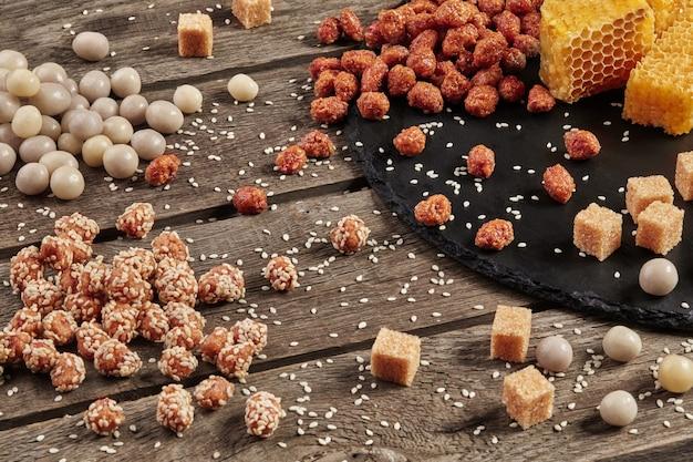 Amendoim cristalizado na mesa de madeira com cubos de açúcar de favos de mel e gergelim
