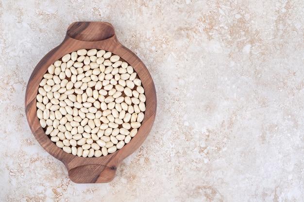 Amendoim descascado em uma placa de madeira, no mármore.