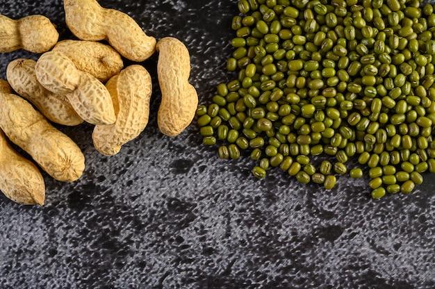 Amendoim e feijão de mung em um piso de cimento preto.
