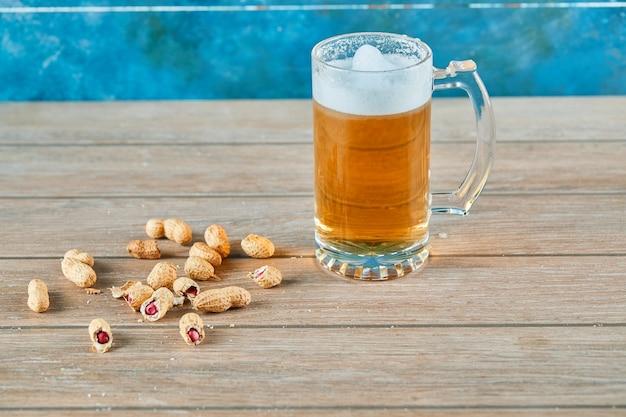 Amendoim e um copo de cerveja na mesa de madeira.