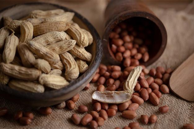 Amendoim em poucas palavras em um pedaço de tigela de madeira e amendoins descascados em pano de saco