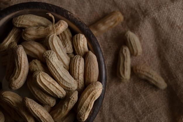 Amendoim em poucas palavras em um pedaço de tigela de madeira em pano de saco